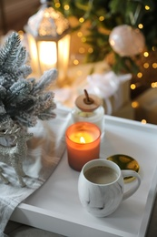 Cup of cocoa, candle and decorative deer on tray at home. Christmas celebration