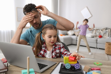 Children disturbing stressed man in living room. Working from home during quarantine