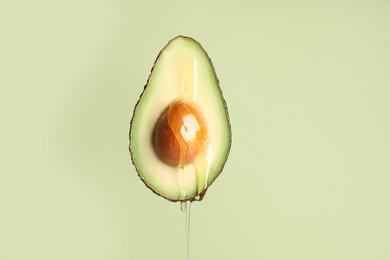 Pouring essential oil onto cut avocado on light green background