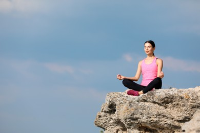 Young woman meditating on cliff. Space for text