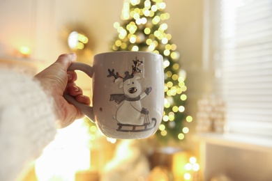Woman with cup of drink and blurred Christmas tree on background, closeup