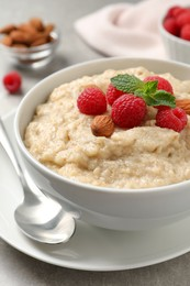 Tasty oatmeal porridge with raspberries and almond nuts served on table, closeup
