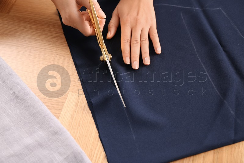 Woman cutting blue fabric with scissors at wooden table, closeup