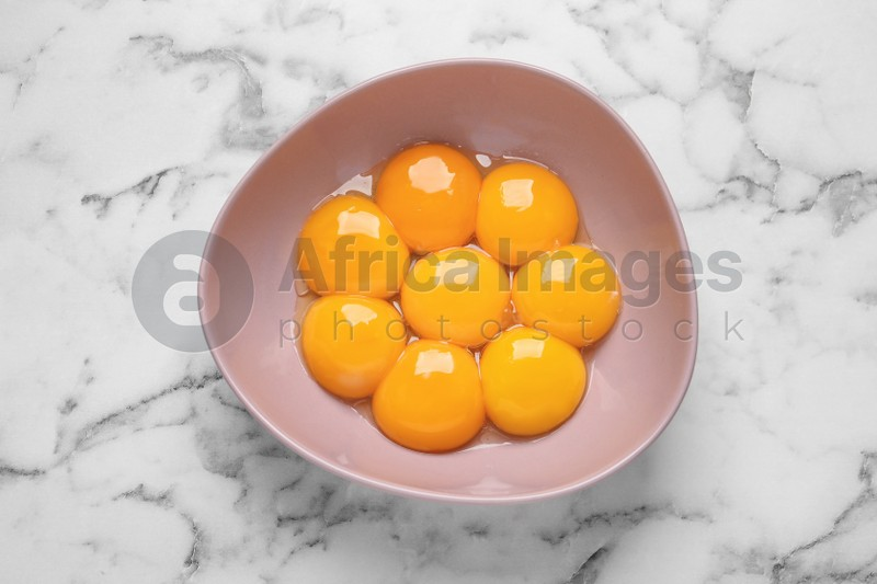 Bowl with raw egg yolks on white marble table, top view