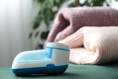 Modern fabric shaver and woolen sweaters indoors, closeup. Space for text