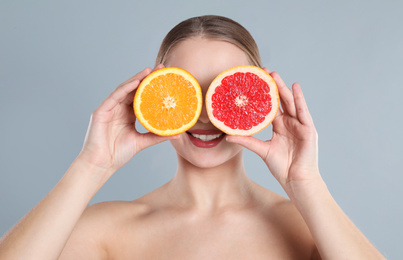Young woman with cut orange and grapefruit on grey background. Vitamin rich food