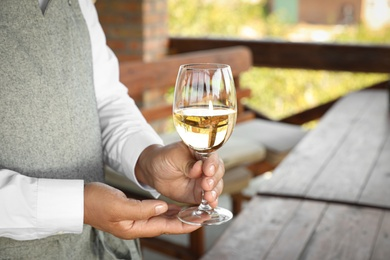 Waiter holding glass of white wine in outdoor cafe, closeup