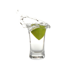 Splashing Mexican Tequila in shot glass with lime slice isolated on white