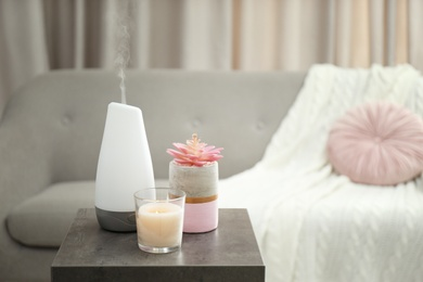 Aroma oil diffuser and candle on table in room