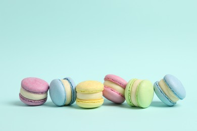 Delicious colorful macarons on light blue background, space for text