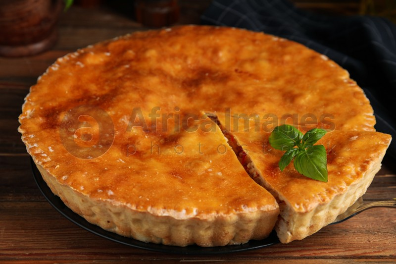 Delicious pie with meat and basil on wooden table