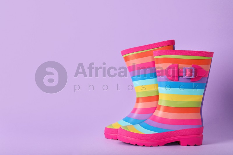 Pair of striped rubber boots on violet background, Space for text