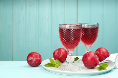 Delicious plum liquor, ripe fruits and mint on table against light blue background, space for text. Homemade strong alcoholic beverage