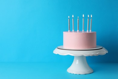 Birthday cake with burning candles on light blue background, space for text