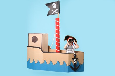 Little boy playing with binoculars in pirate cardboard ship on turquoise background
