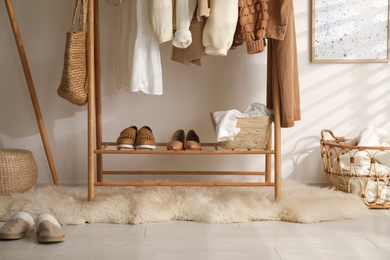 Rack with stylish shoes and women's clothes in dressing room. Modern interior design