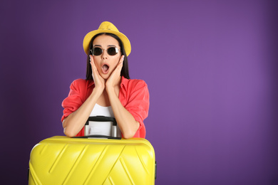 Beautiful surprised woman with suitcase for summer trip on purple background. Vacation travel