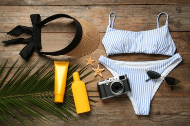 Flat lay composition with beach accessories on wooden background