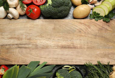Fresh products and wooden board with space for text, flat lay. Healthy cooking