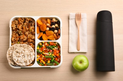 Flat lay composition with thermos and lunch box on wooden background