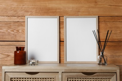 Empty frames with other decor on table near wooden wall. Mockup for design