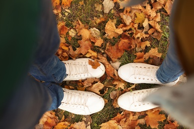 Couple standing on ground covered with leaves in park, above view. Autumn walk