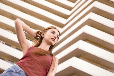 Beautiful young woman at modern building, low angle view