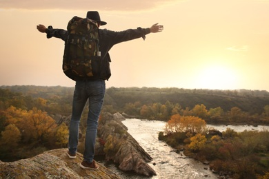 Traveler with backpack enjoying beautiful view near mountain river. Autumn vacation