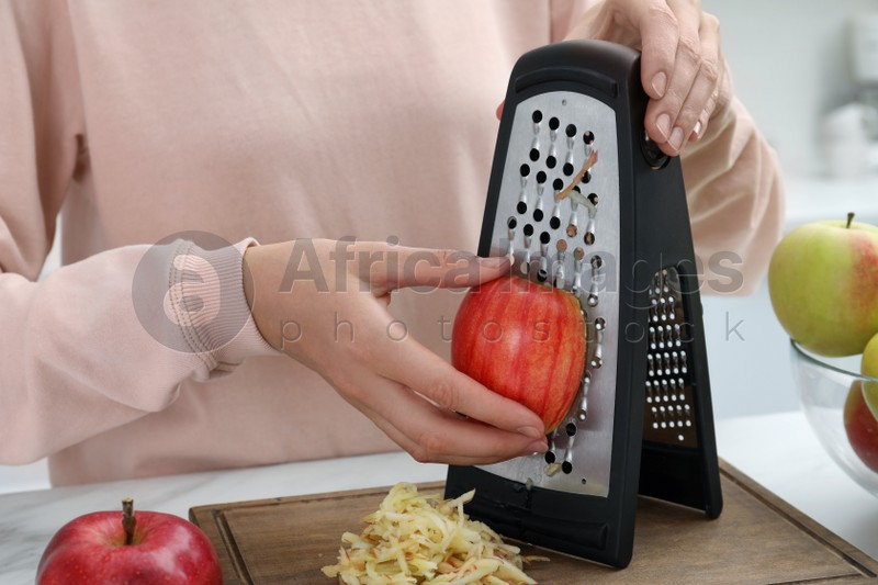 Woman grating fresh red apple at kitchen table, closeup