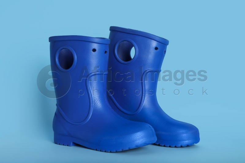Pair of bright rubber boots on light blue background