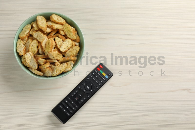 Modern tv remote control and rusks on white wooden table, flat lay. Space for text