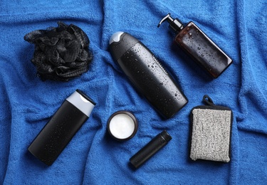 Flat lay composition with men's cosmetics on blue towel