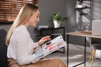Happy woman reading interesting magazine in office
