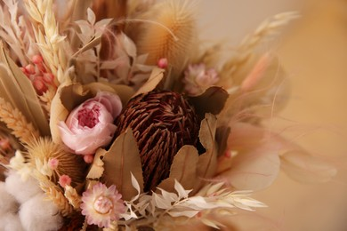 Bouquet of dry flowers and leaves on blurred background, closeup