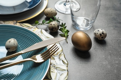 Festive Easter table setting with eggs on color background