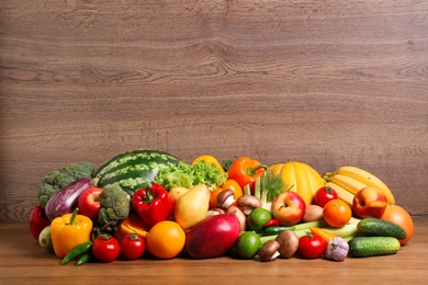 Assortment of fresh organic fruits and vegetables on wooden table. Space for text