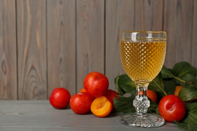 Delicious plum liquor and ripe fruits on grey wooden table, space for text. Homemade strong alcoholic beverage