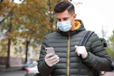 Man in medical face mask and gloves with smartphone walking outdoors. Personal protection during COVID-19 pandemic