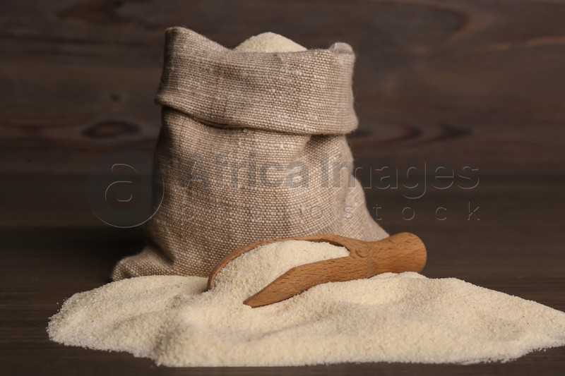 Bag and scoop with uncooked organic semolina on wooden table