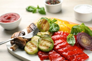 Delicious grilled vegetables on white wooden table, closeup