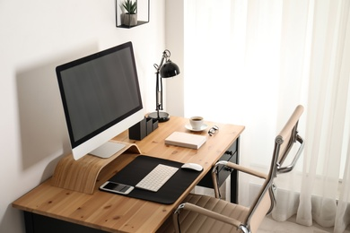 Stylish workplace interior with modern computer on table. Mockup for design