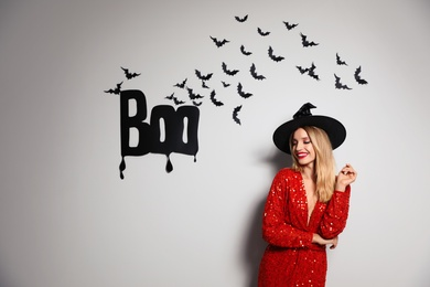 Woman in witch hat posing near white wall decorated for Halloween