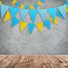 Empty wooden table and decorative bunting flags hanging on grey wall