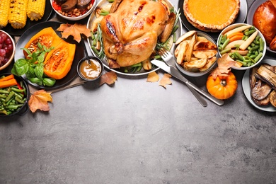Traditional Thanksgiving day feast with delicious cooked turkey and other seasonal dishes served on grey table, flat lay. Space for text