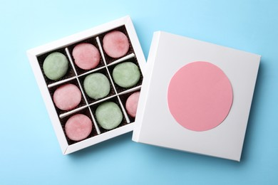 Many different delicious mochi in box on light blue background, top view. Traditional Japanese dessert