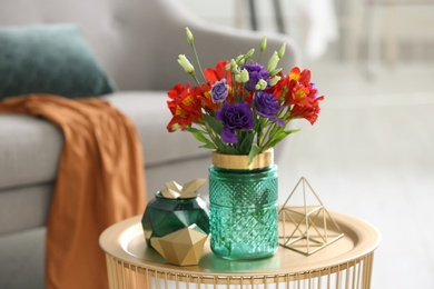 Glass vase with fresh flowers on table in living room
