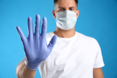 Man in protective face mask and medical gloves showing stop gesture against blue background, focus on hand