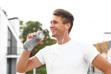 Young man with earphones drinking water after running on street. Healthy lifestyle