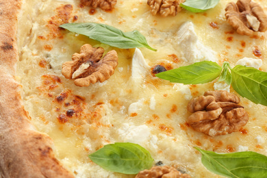 Delicious cheese pizza with walnuts and basil as background, closeup