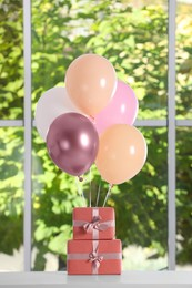 Bunch of color balloons and beautifully wrapped gift boxes on white table near window